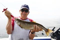 Mann, der große Fische - See-Forelle wiegt Lizenzfreie Stockfotos