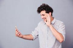 Mann, der Grußgeste auf Web-Kamera zeigt Lizenzfreies Stockbild