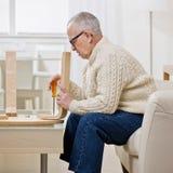 Mann, der hölzerne Tabelle unter Verwendung des Schraubendrehers konstruiert Stockfoto