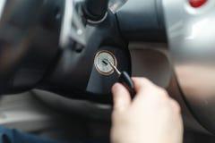 Mann der Hand s schließen einen Schlüssel an, der die Maschine eines Autos anläßt Stockfotografie