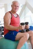 Mann, der Handgewichte auf Schweizer Kugel an der Gymnastik verwendet Stockbild