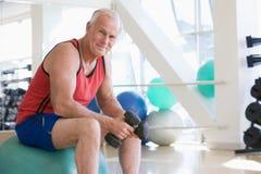 Mann, der Handgewichte auf Schweizer Kugel an der Gymnastik verwendet Stockbilder