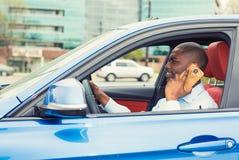 Mann, der Handy beim Fahren des Autos zur Arbeit verwendet Lizenzfreies Stockfoto