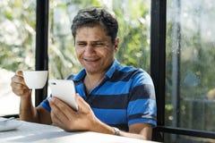 Mann, der Handy beim Haben des heißen Getränks verwendet stockfotos