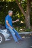 Mann, der Handy nach Autozusammenbruch betrachtet Lizenzfreie Stockfotografie