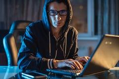 Mann in der Haube, die in der Kamera schaut Hackerangriffe und Diebstahl von Zugangsdatenbanken mit Passw?rtern Abstrakter Hinter lizenzfreies stockfoto