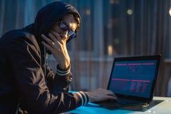 Mann in der Haube, die in der Kamera schaut Hackerangriffe und Diebstahl von Zugangsdatenbanken mit Passw?rtern Abstrakter Hinter stockfotografie
