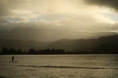 Mann, der in Hawaii am dunstigen Nachmittag paddleboarding ist Stockfotos
