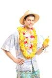 Mann in der hawaiischen Kleidung, die ein Cocktail hält Lizenzfreies Stockfoto