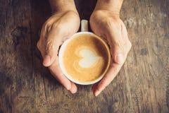 Mann, der heißen Tasse Kaffee hält Stockfotos