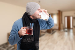Mann, der heißen Tee trinkt und Nase abwischt Lizenzfreies Stockbild