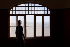 Mann, der heraus ein schmutziges Fenster anstarrt Lizenzfreie Stockfotos
