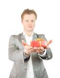Mann, der heraus einen roten anwesenden Kasten anhält Lizenzfreies Stockbild