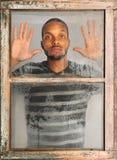Mann, der heraus Fenster schaut Stockfotografie