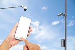Mann, der heraus mobile intelligente Telefonsteuertür Überwachungskamera verwendet betrüger lizenzfreie stockfotografie