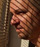 Mann, der heraus zwar Vorhänge eines Fensters schaut Stockfotografie