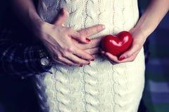 Mann, der Herzform der schwangeren Frauen hält Stockfotos