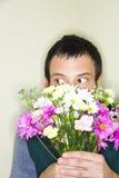 Mann, der hinter Blumenstrauß sich versteckt Stockfotografie