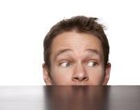 Mann, der hinter Schreibtisch sich versteckt Lizenzfreie Stockbilder