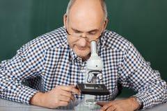 Mann, der hinunter ein Mikroskop schaut Lizenzfreie Stockfotos