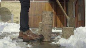 Mann, der Holz für das Hacken im Schneeyard vorbereitet stock footage