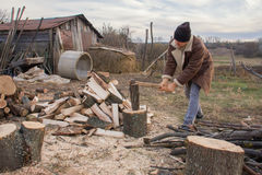 Mann, der Holz im Dorf hackt Stockfotografie