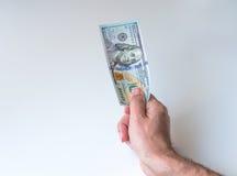 Mann, der hundert US-Dollars gibt Stockfotos