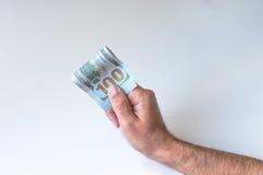 Mann, der hundert US-Dollars hält Stockfotografie