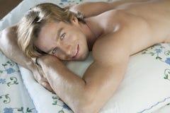 Mann, der im Bett lächelt Stockbild