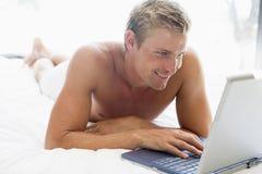 Mann, der im Bett mit Laptop liegt Lizenzfreie Stockfotos