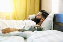 Mann, der im Bett und in trinkendem Kaffee liegt Stockfotografie