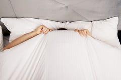 Mann, der im Bett unter Blättern sich versteckt Lizenzfreie Stockfotografie