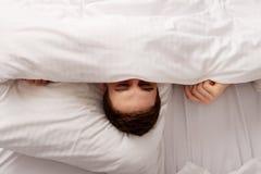 Mann, der im Bett unter Blättern sich versteckt Lizenzfreie Stockfotos