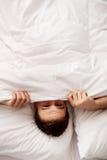 Mann, der im Bett unter Blättern sich versteckt Lizenzfreies Stockfoto