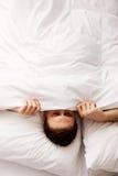 Mann, der im Bett unter Blättern sich versteckt Stockbilder