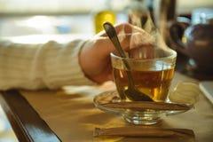 Mann, der im caffe und in trinkendem Tee stationiert Stockfotografie