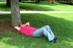 Mann, der im Farbton unter einem Baum Nickerchen macht stockfotografie