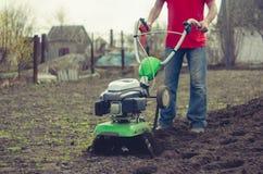 Mann, der im Frühjahr Garten mit Pflügermaschine bearbeitet Lizenzfreie Stockfotos