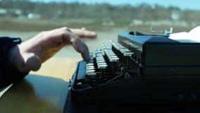 Mann, der im Freien auf einer alten Schreibmaschine mit seinen Händen schreibt stock video