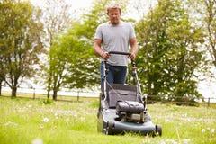 Mann, der im Garten-Ausschnitt-Gras mit Rasenmäher arbeitet Lizenzfreie Stockfotografie