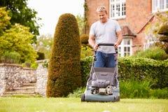 Mann, der im Garten-Ausschnitt-Gras mit Rasenmäher arbeitet Stockfotos