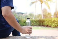 Mann, der im Garten mit einer Flasche Trinkwasser sitzt stockfoto