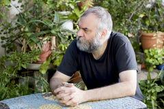 Mann, der im Garten sitzt stockbild