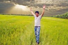 Mann, der im grünen Reis steht Stockbild