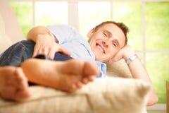 Mann, der im Haus sich entspannt stockbild