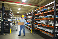 Mann, der im industriellen Herstellungs-Lager arbeitet Stockfotos
