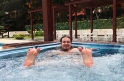 Mann, der im Jacuzzi sich entspannt Lizenzfreies Stockfoto