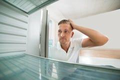 Mann, der im leeren Kühlschrank schaut Lizenzfreie Stockfotografie