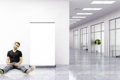 Mann, der im modernen Büro sitzt Stockbild