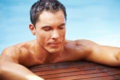 Mann, der im Pool sich entspannt Stockfotos